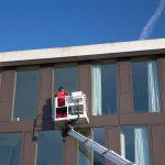 Kollege vom Erich Bauer GmbH Team im Fensterputzkorb auf dem Steiger